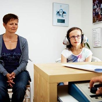 Pige til lydterapi. Får lavet høreprøve med sin mor i baggrunden.