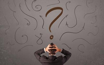 Forretningsmand overvældet af muligheder. Ser op på væg med en masse pile og et stort spørgsmålstegn.